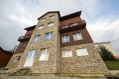 Façade de nouvelle maison en bois de cottage des matériaux et de la pierre de bois de charpente avec le balcon décoratif sur le f images libres de droits