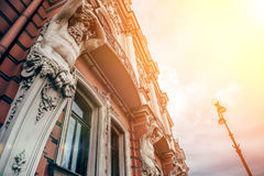 Façade du vieux bâtiment à St Petersburg avec des statues des titans en soleil Images libres de droits