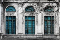 Façade du vieux bâtiment abandonné avec trois grandes fenêtres arquées de verre et de colonnes bleus Fond monochrome Photo libre de droits