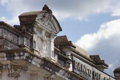 Façade en pierre découpée de bâtiment contre le ciel nuageux Image libre de droits