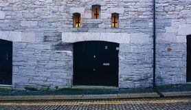 Façade en pierre de bâtiment avec petit Windows Image stock