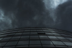 Façade en verre de bâtiment de courbe sous le nuage de pluie Photo libre de droits
