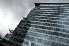 Façade en verre de construction contre le ciel nuageux Image stock