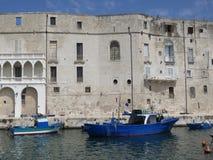 Façade et quai dans Polignano une jument avec des bateaux et des attirails de pêche photo libre de droits