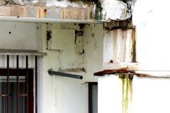 Façade faisante le coin blanche criquée délabrée sale de bâtiment avec les barres rouillées en métal sur les fenêtres et le béton images libres de droits