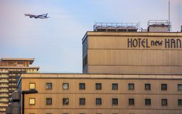 Façade of the hotel and a plane flying over it. Travel around Japan. 2013.01.05, Osaka, Japan. Façade of the hotel and a plane flying over it. Travel royalty free stock images