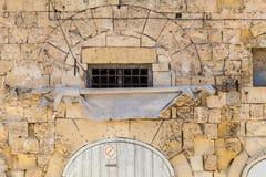Façade maltaise antique de maison de chaux avec la voûte et l'aw frangé Photographie stock libre de droits