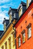 Façade rouge et jaune des constructions avec des hublots Photos stock
