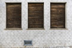 Façade tiled, weathered with soffit with closed wooden shutters weathered and sill made of chip concrete. Seems uninhabited royalty free stock photos