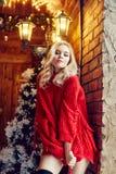Façonnez à femme sexy la blonde dans le chandail rouge, en ayant l'amusement et en posant contre l'arbre de Noël et un hiver de l photographie stock