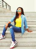 Façonnez à jeune port africain de femme les lunettes de soleil et la chemise de jeans se reposant sur des escaliers dans la ville Photographie stock libre de droits