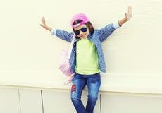 Façonnez à port d'enfant de petite fille les lunettes de soleil et la casquette de baseball dans la ville au-dessus du blanc Photos libres de droits