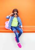 Façonnez à port d'enfant de petite fille les lunettes de soleil, la chemise, les jeans et le sac à dos au-dessus de l'orange colo Photos stock