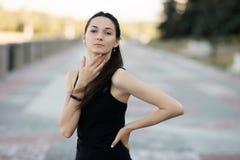 Façonnez à portrait de mode de vie la jeune brune jolie femme posant le soir de coucher du soleil d'été de quai de ville montrant Image stock