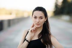 Façonnez à portrait de mode de vie la jeune brune jolie femme posant le soir de coucher du soleil d'été de quai de ville montrant Photographie stock libre de droits