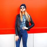 Façonnez à portrait la belle femme blonde dans le style de noir de roche sur un fond rouge dans la ville images libres de droits