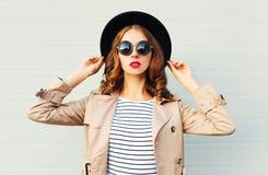 Façonnez à portrait la jolie femme avec les lèvres rouges utilisant des lunettes de soleil d'un chapeau noir au-dessus de gris Images stock