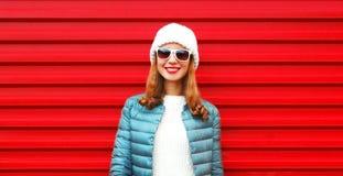 Façonnez à portrait la jolie femme de sourire sur un fond rouge Photos stock