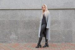 Façonnez à style la jeune femme élégante dans le manteau de fourrure gris marchant à la rue de ville images stock
