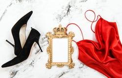 Façonnez aux talons hauts rouges de noir de robe étendus par appartement le cadre d'or Image libre de droits