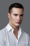 Façonnez l'homme de beauté dans la chemise blanche sur le fond gris Photographie stock