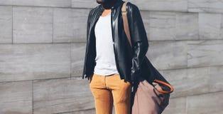 Façonnez l'homme portant un cycliste noir la veste en cuir avec le sac image stock