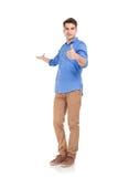 Façonnez l'homme te souhaitant la bienvenue tout en montrant les pouces lèvent le geste images stock