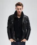 Façonnez l'homme, veste en cuir de modèle, fond gris Images stock