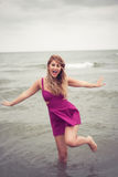 Façonnez la blonde à la pose de côté de mer de plage sans chaussure dans l'eau Images libres de droits