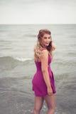 Façonnez la blonde sur le côté de mer de plage posant dans l'eau Photo stock