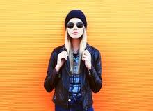 Façonnez la femme assez blonde de portrait dans le style de noir de roche sur un fond orange coloré Photographie stock