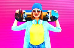 Façonnez la femme assez de sourire avec une planche à roulettes dans la ville sur le rose photo stock