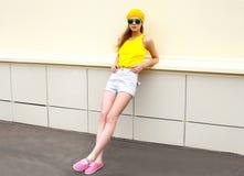 Façonnez la femme assez fraîche dans les lunettes de soleil et des vêtements colorés jaunes au-dessus de blanc Photographie stock