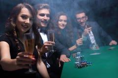 Façonnez la femme avec des verres de vin, se reposant à une table dans un casino Photo stock