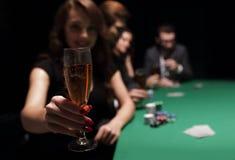 Façonnez la femme avec des verres de vin, se reposant à une table dans un casino Image libre de droits