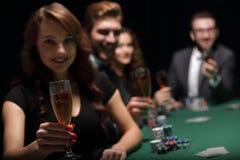 Façonnez la femme avec des verres de vin, se reposant à une table dans un casino Images stock