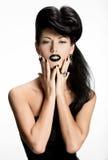 Façonnez la femme avec les clous et les lèvres noirs dans la couleur noire Photographie stock