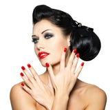 Façonnez la femme avec les languettes rouges, les clous et la coiffure créative Image stock