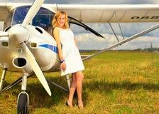 Façonnez la femme beautyful dans l'avion ultra-léger voisin de robe blanche image stock