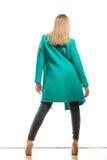 Façonnez la femme dans la vue arrière de couleur de manteau vif de vert Photographie stock