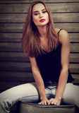 Façonnez la femme de maquillage avec la longue coiffure en les blues-jean et le rouge image stock