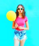 Façonnez la femme de portrait utilisant un T-shirt, shorts de denim avec le ballon à air jaune au-dessus du bleu coloré Image libre de droits