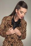 Façonnez la femme fixant son collier tout en regardant vers le bas Photo stock