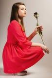 Façonnez la femme la fille que de l'adolescence dans la robe rouge avec sec s'est levée photo stock