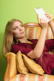 Façonnez la femme s'étendant sur le sofa avec le comprimé de PC Photographie stock libre de droits
