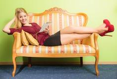 Façonnez la femme s'étendant sur le sofa avec le comprimé de PC Images libres de droits
