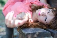 Façonnez la femme se trouvant sur le banc, avec un vêtement rose de morceau Images libres de droits