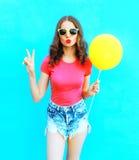 Façonnez la femme utilisant un T-shirt, shorts de denim avec le ballon à air jaune au-dessus du bleu coloré Images stock