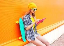 Façonnez la fille assez fraîche à l'aide du PC de comprimé avec la planche à roulettes au-dessus de l'orange colorée Photos libres de droits