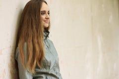 Façonnez la fille avec de longs cheveux utilisant la jupe noire, le manteau de fossé et la veste en cuir grise Photographie stock libre de droits